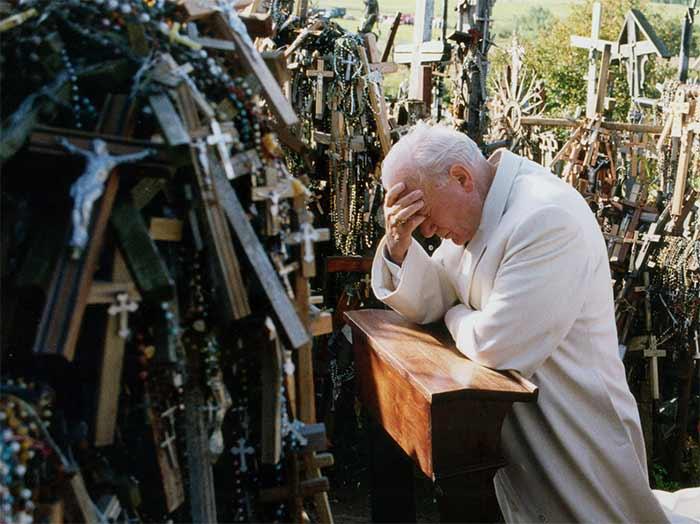 San Juan Pablo II rezando de rodillas frente a cruces