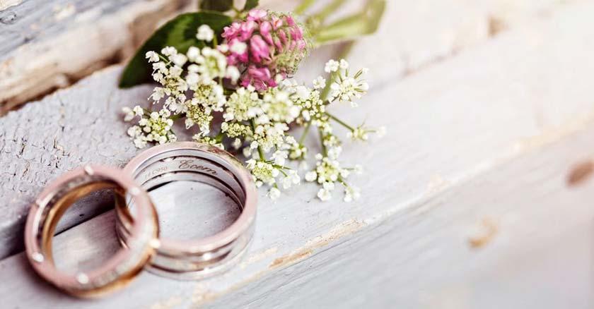 anillos de matrimonio sobre mesa de madera al lado de flores