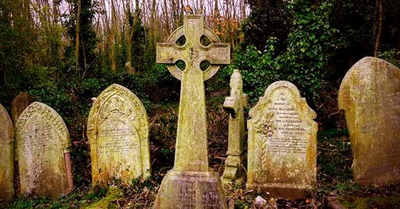 cruz en cementerio lapidas tumbas arboles
