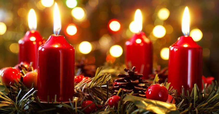 cuatros velas rojas encendidas sobre adornos de navidad luz dorada