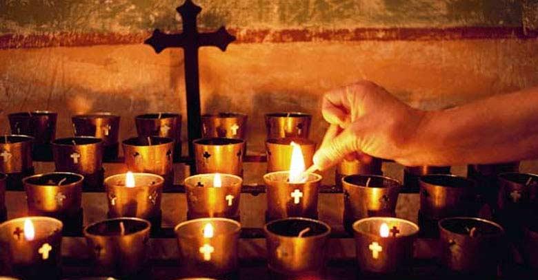 encendiendo velas difuntos crucifijo oscuro