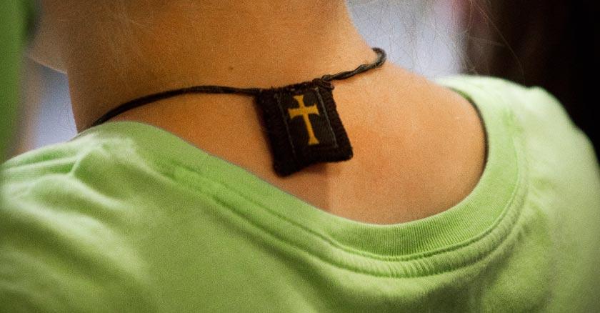 escapulario marron con cruz amarilla en la parte de atras del cuello de una chica