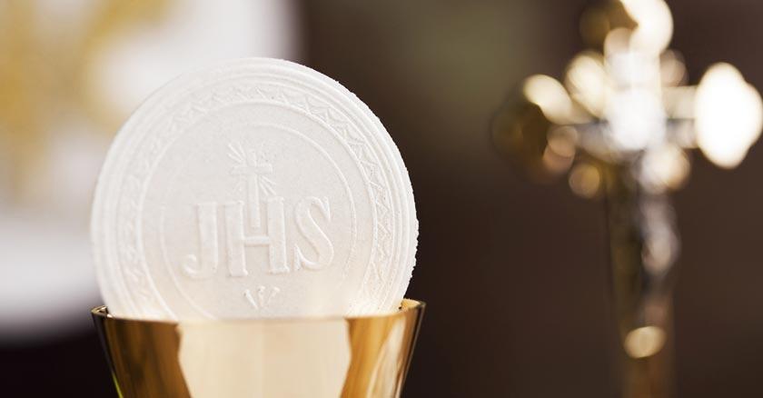 eucaristia dentro de copon de vino sagrado hostia jhs hs cruz de fondo