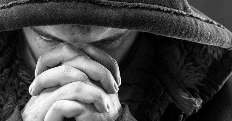 hombre orando con capucha blanco y negro