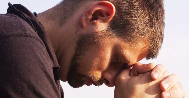 hombre rezando con ojos cerrados manos juntas
