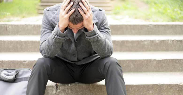 hombre sentado en escalera deprimido triste inseguro manos en la cabeza