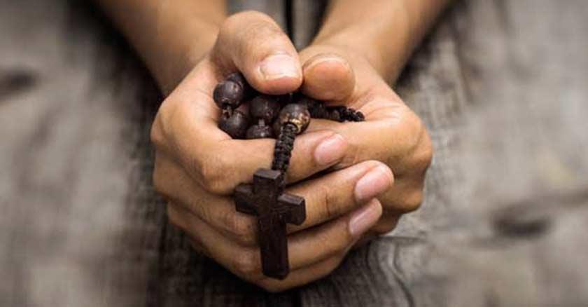 hombre sosteniendo un rosario de madera oscura entre sus manos