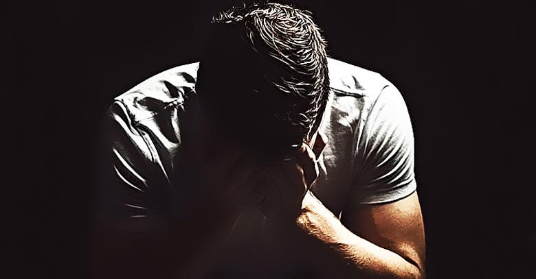 hombre triste preocupado con manos en el rostro fondo oscuro