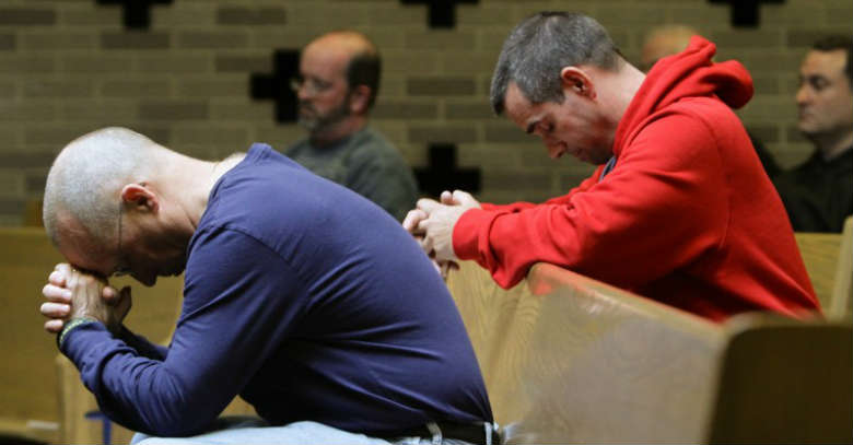 hombres rezando iglesia