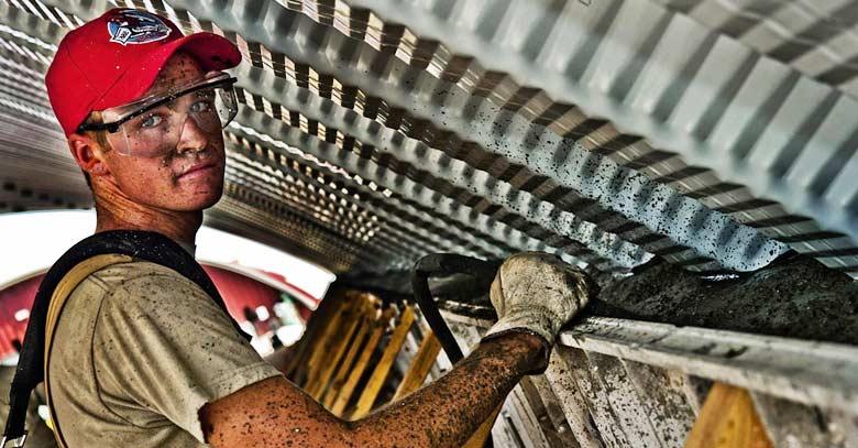 joven obrero trabajando con lentes de proteccion construyendo