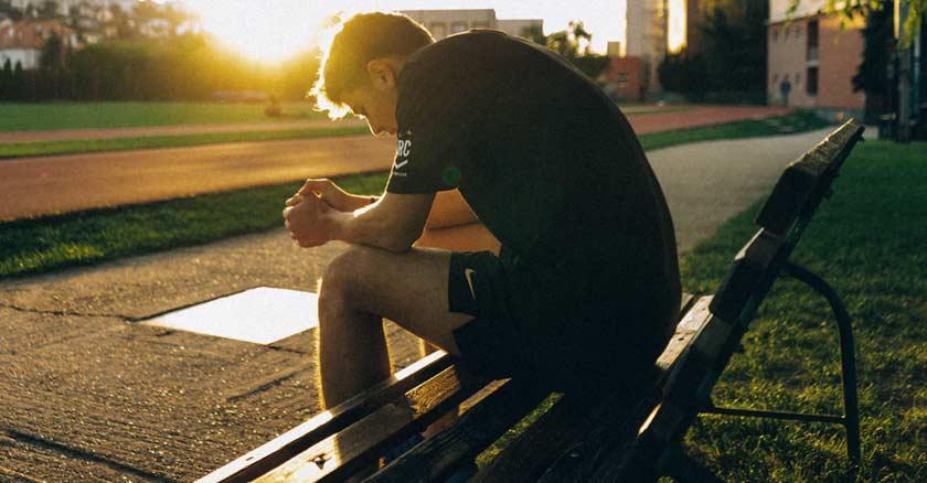 joven sentando en una banca solo triste deprimido puesta de sol