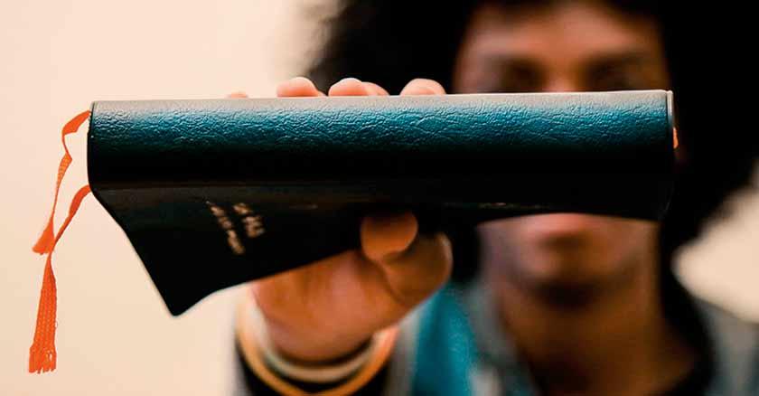 joven sosteniendo libro en su mano libros que todo catolico deberia leer