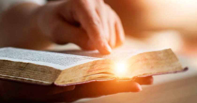 mano de hombre leyendo la biblia reflejo de luz en hojas enemigos del alma