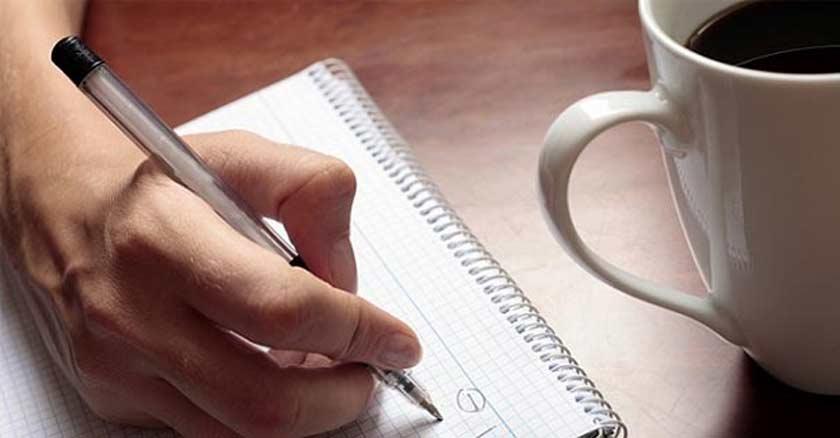 mano-de-hombre-redactando-algo-en-un-cuaderno-taza-de-cafe-al-lado.jpg
