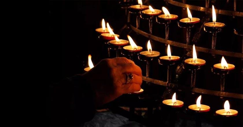 mano de una persona en la oscuridad encendiendo muchas velas para orar