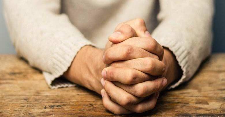 manos de hombre juntas rezando sobre tabla de mesa