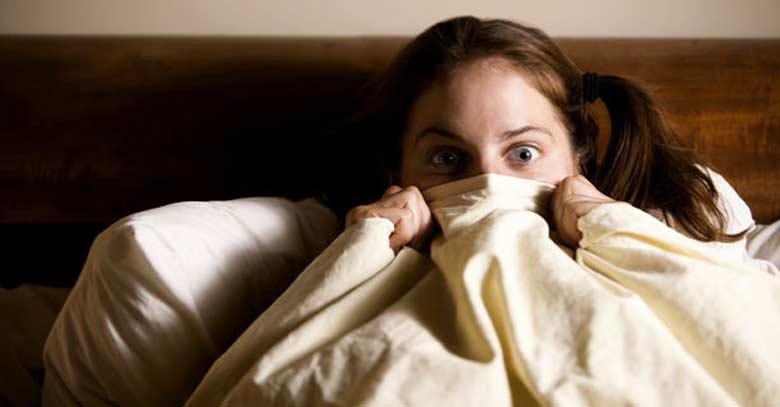 mujer asustada en cama por pesadilla