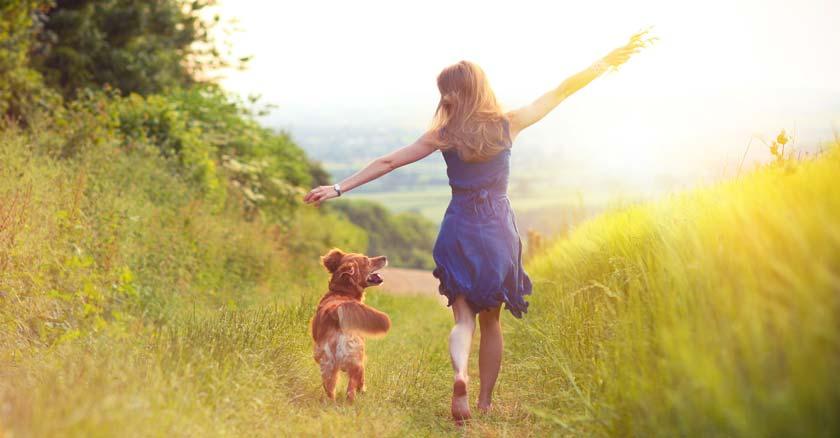 mujer caminando feliz al lado de su perro por verdes praderas