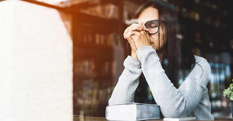 mujer con lentes sentadan oracion en bliblioteca