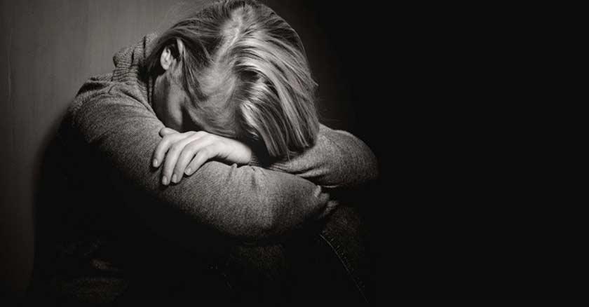 mujer deprimida sentada recostada contra una pared rostro en sus piernas triste depresion