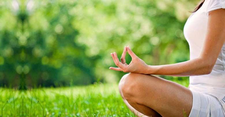 mujer practicando posicion de yoga en jardin fondo verde