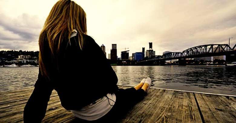 mujer recostada en un muelle mirando mar barcos