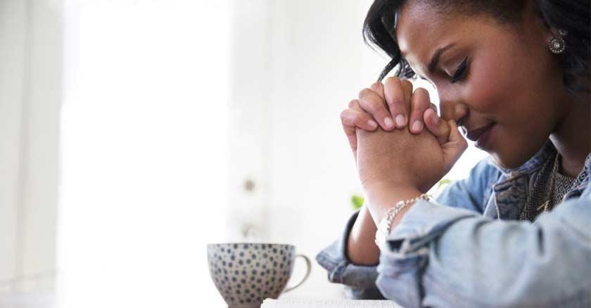 mujer rezando orando con las manos juntas y ojos cerrados en la mesa taza de cafe