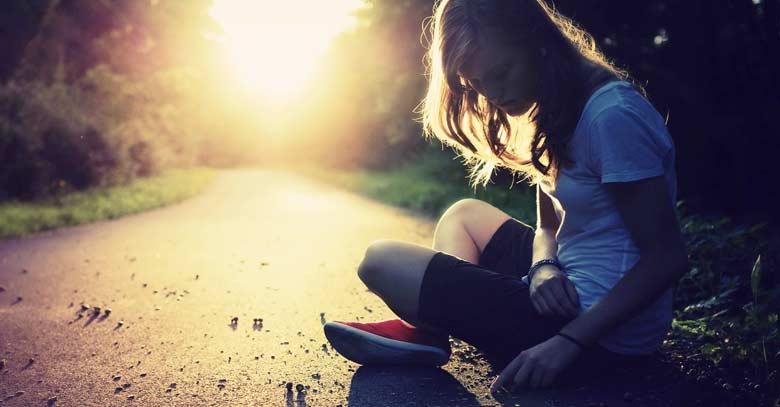 mujer sentada en carretera ocaso luz del sol