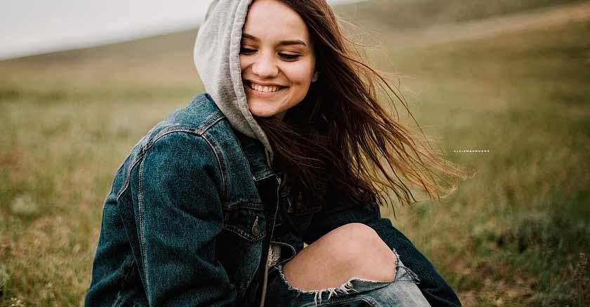 mujer sentada en cesped pradera sonriendo recuperar la paz del corazon
