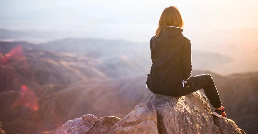 mujer sentada en la cima de una montana viendo el horizonte ocaso sol