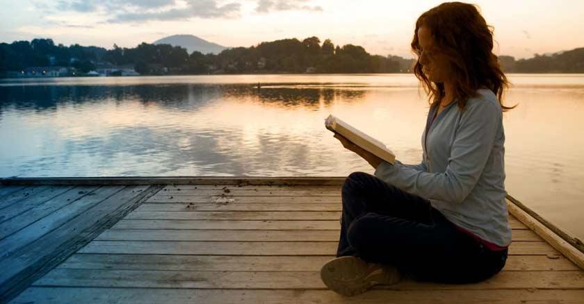 mujer-sentada-en-un-muelle-orilla-de-un-lago-leyendo-la-biblia-en-mano-ocaso.jpg