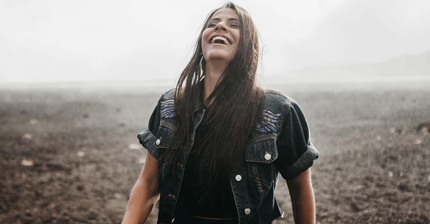 mujer sonriendo muy feliz fondo rocas naturaleza