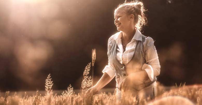 mujer sonriente en el campo flores color sepia