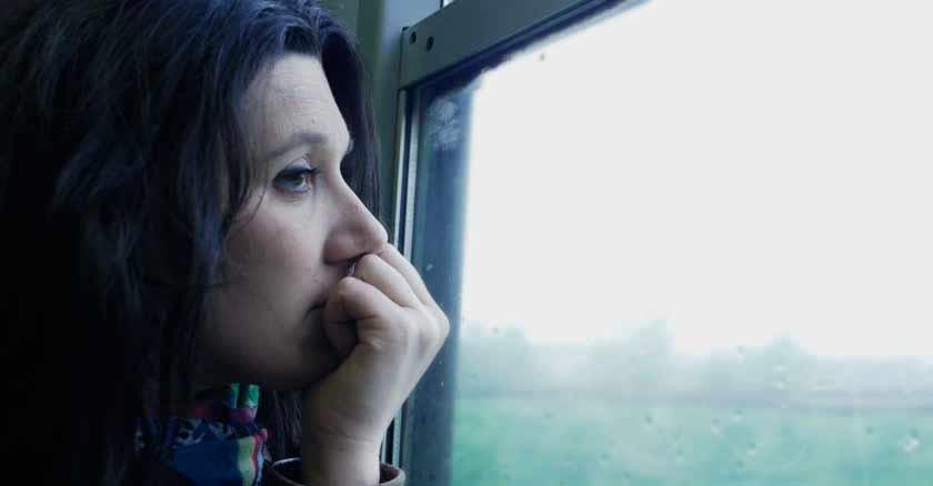 mujer triste mirando ventana como controlar las emociones educando las emociones