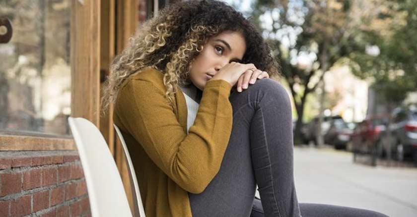 mujer triste sentada en una banca en la acera sola soledad