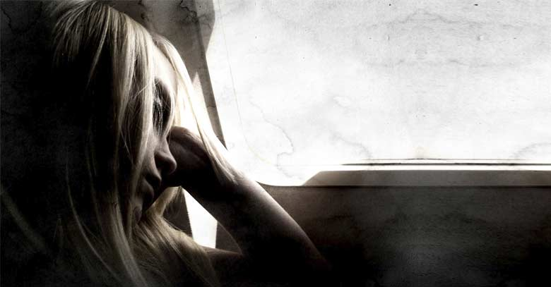 mujer tristeza al lado de ventana
