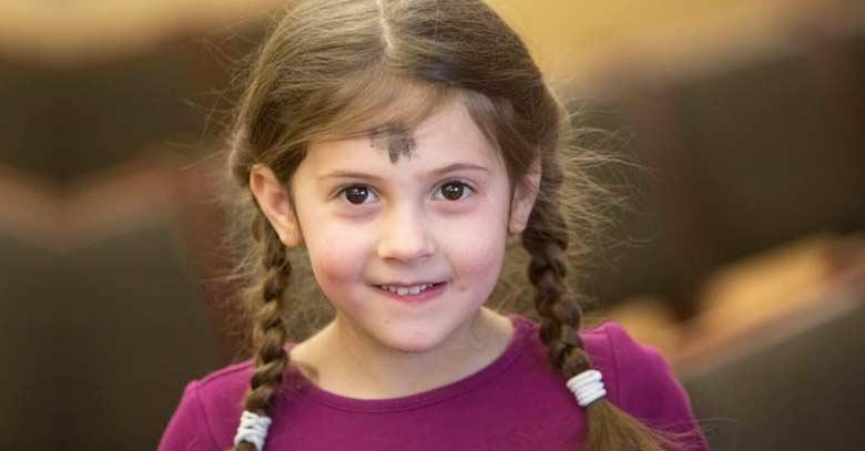 nina con cruz de cenizas en su frente sonriendo