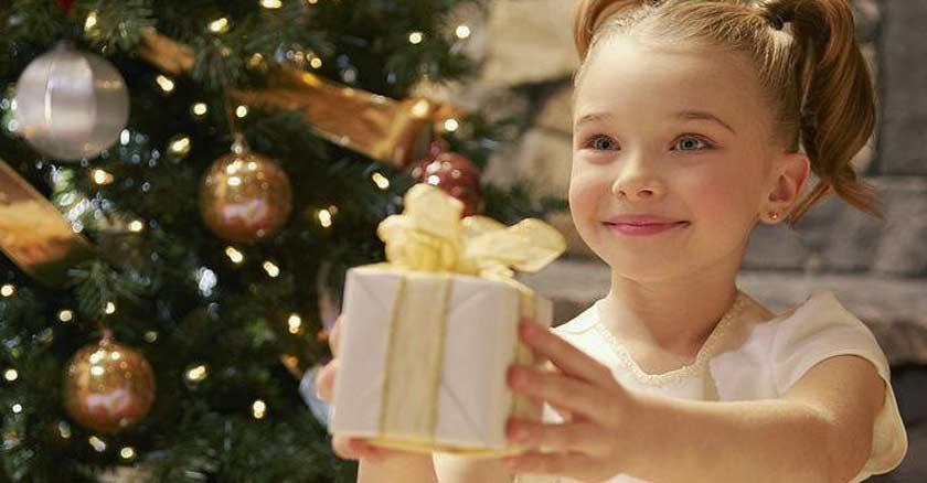 nina con un regalo entre sus manos dando a una persona fondo arbol de navidad