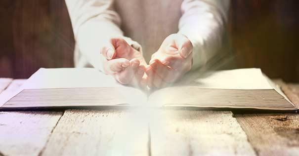 orando manos abiertas sobre la biblia