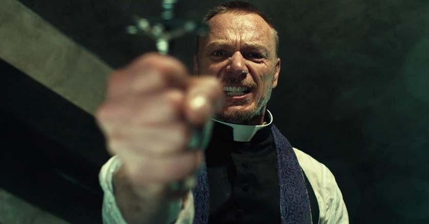 padre sostiene una cruz haciendo un rito de exorcismo demonio
