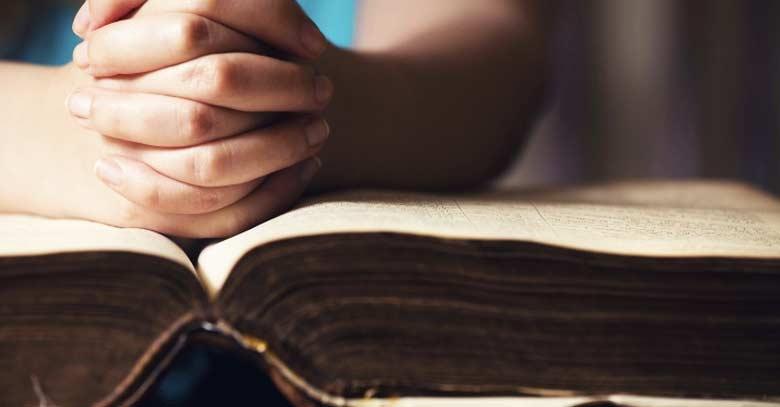 persona en oracion con manos juntas sobre la biblia