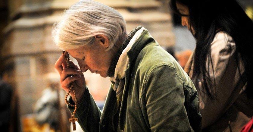 persona mayor con rosario en mano rezando senal de la cruz