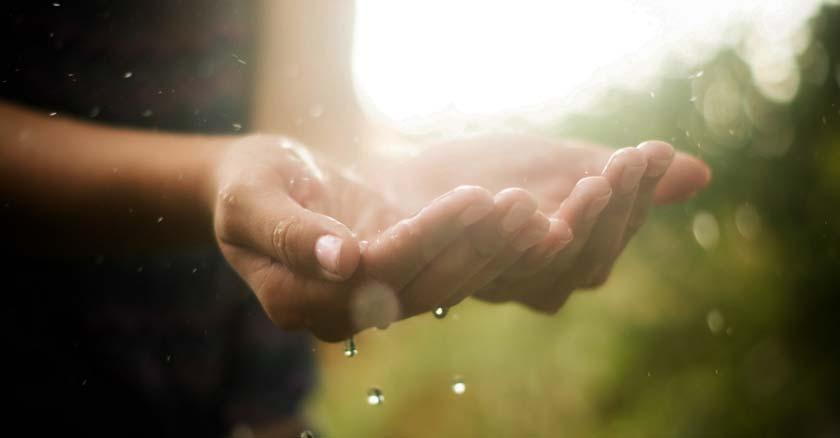 persona poniendo las manos hacia arriba con palmas para sostener agua lluvia