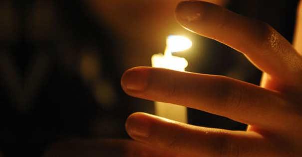 persona sosteniendo vela con su mano oracion