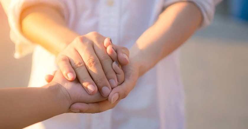 persona tomando con sus dos manos la mano de otra persona ayuda