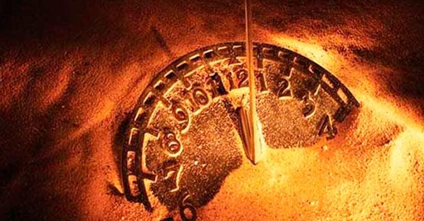 reloj de piedra en la arena fin del mundo