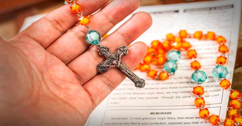 rosario en las manos sostiene un rosario colorido rezar el rosario es poderoso
