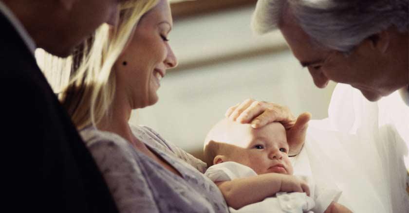 sacerdote colocando su mano sobre la frente de un bebe mama papa sonrien