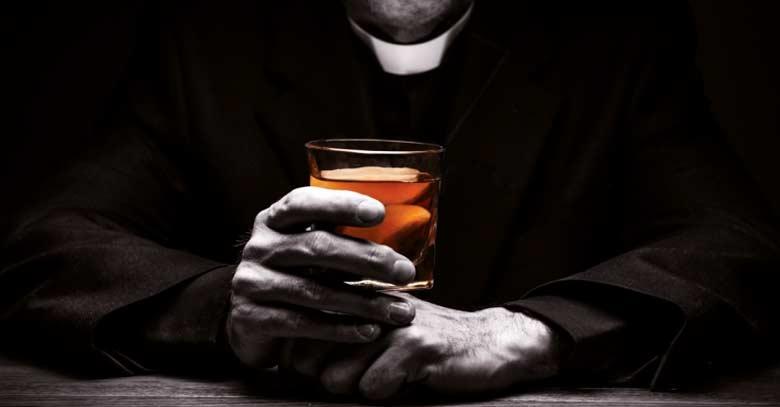 sacerdote con vaso de alcohol en su mano