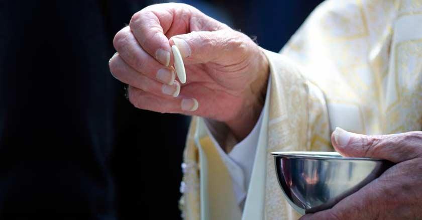sacerdote tomando una hostia con su mano de la patena para dar comunion caliz